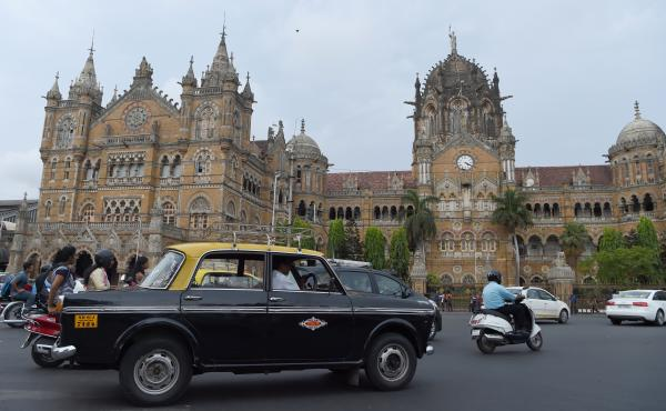 An Indian taxi driver drives his Premier Padmini past the iconic building Chhatrapati Shivaji Terminus railway station in Mumbai, India.
