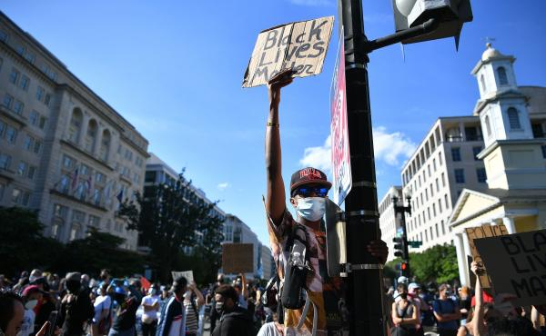 Demonstrators protesting the death of George Floyd hold up placards near the White House on June 1 in Washington, D.C.