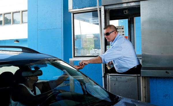 Toll booth cashier Henry Gregorio collects change from drivers at the New Rochelle Toll Plaza on I-95. Gregorio has worked in a toll booth since 1980. Toll booths are gradually being replaced by E-ZPass technology.