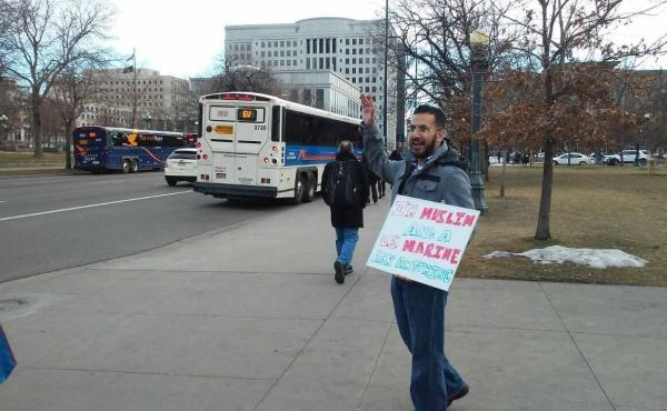 """Mansoor Shams stands in downtown Denver with his sign, """"I'm A Muslim U.S. Marine Ask Anything."""" He is traveling the country in an effort to dispel misconceptions about Muslims."""