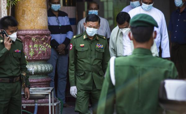 Myanmar's de facto leader, Aung San Suu Kyi, is charged with illegally importing walkie-talkie radios, in the first formal charges against her since the military ordered her detention. Here, a military commander visits a Hindu temple in Yangon.