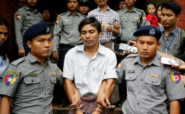 Reuters journalists Kyaw Soe Oo and Wa Lone were escorted by police after a court hearing in August 2018 in Yangon, Myanmar.