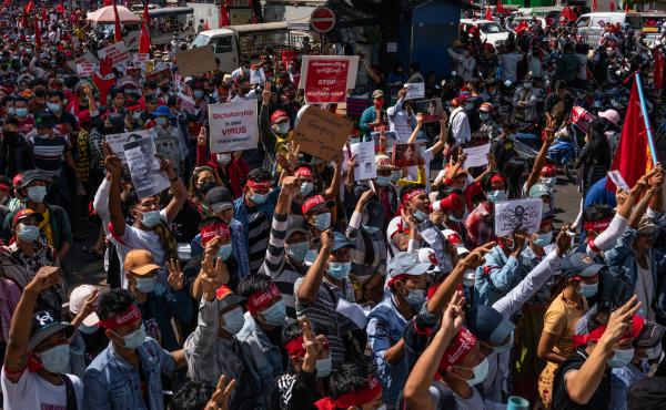 Protesters hold placards and shout slogans on Saturday in Yangon, Myanmar. Myanmar declared martial law in parts of the country, including its two largest cities, as protests continued to draw people to the streets after the military staged a coup.