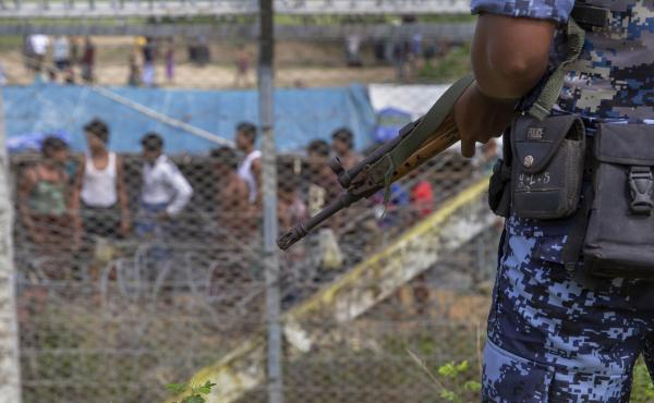 "Myanmar border guard police patrol the fence in the ""no man's land"" zone between Myanmar and Bangladesh, as seen from Maungdaw, Rakhine state, during a government-organized visit for journalists on Aug. 24. A new U.N. report finds that Myanmar's military"