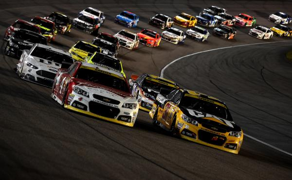 NASCAR drivers Kevin Harvick (in car on left) and Ryan Newman lead the pack during the Sprint Cup Series Ford EcoBoost 400 at Homestead-Miami Speedway on Nov. 16, in Homestead, Fla.