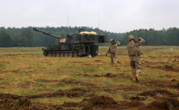 U.S. soldiers carry a 155 mm artillery round for a live-fire training exercise during the Anakonda war games near Olezno, Poland, on June 14.