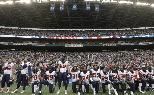 Houston Texans observe the national anthem before a game against the Seattle Seahawks last October, with some players kneeling in protest while others stand.