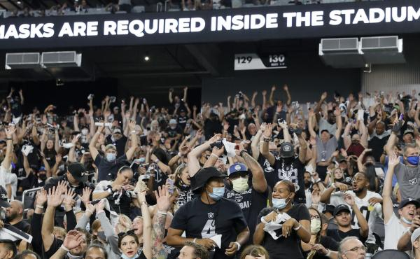 Raiders fans do the wave during last weekend's preseason game in Las Vegas as a stadium sign reminds them to wear face masks. The team now says spectators will have to show proof of vaccination — and that no masks will be required for those who have bee