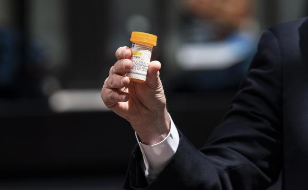 Senate Minority Leader Chuck Schumer, D-N.Y., holds a bottle of hydroxychloroquine while raising concerns about its use.