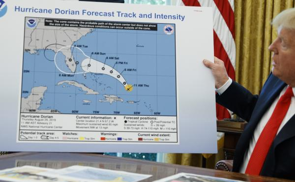 President Trump holds a chart as he talks with reporters after receiving a briefing on Hurricane Dorian in the Oval Office of the White House, on Wednesday in Washington.