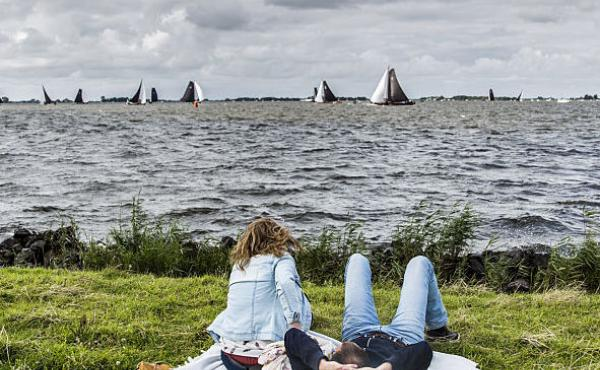 People at leisure watch boats taking part in the sixth race of the Skutsjesilen competition, a traditional boat race of sailing yachts from several Frisian cities, in Elahuizen, on August 5.
