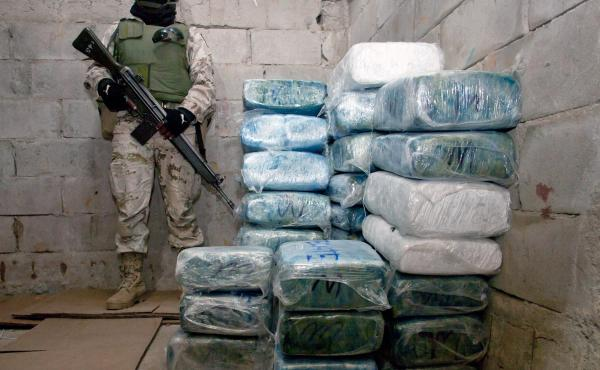 A Mexican soldier stands guard next to marijuana packages in Tijuana following the discovery of a tunnel under the U.S.-Mexico border in 2010.