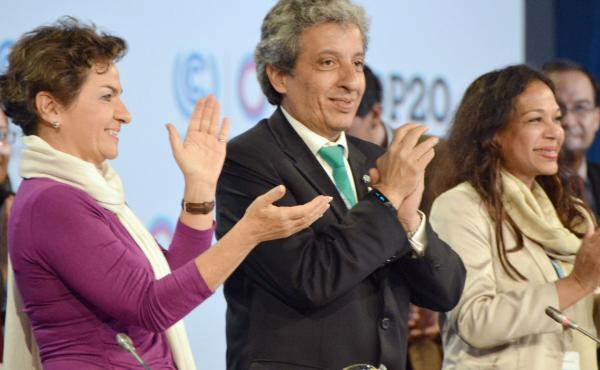 Manuel Pulgar-Vidal (center), Peru's environment minister, applauds on Saturday after delegates to the Lima climate conference agreed on a deal to cut greenhouse gas emissions.