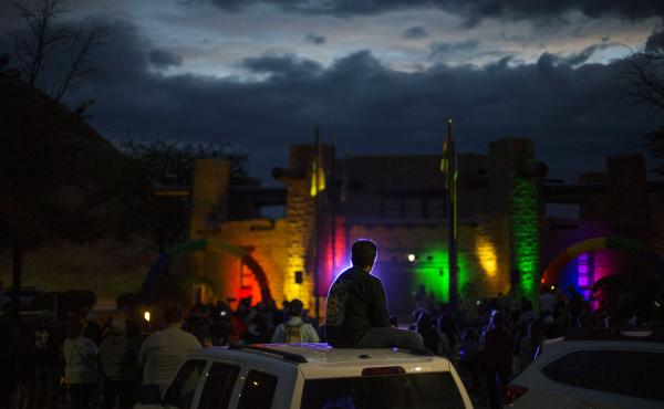 Matthew Slick is silhouetted by the purple light as the Navajo Council Chamber is lit in rainbow colors for Pride on June 28 in Window Rock, Ariz., the capital of the Navajo Nation.