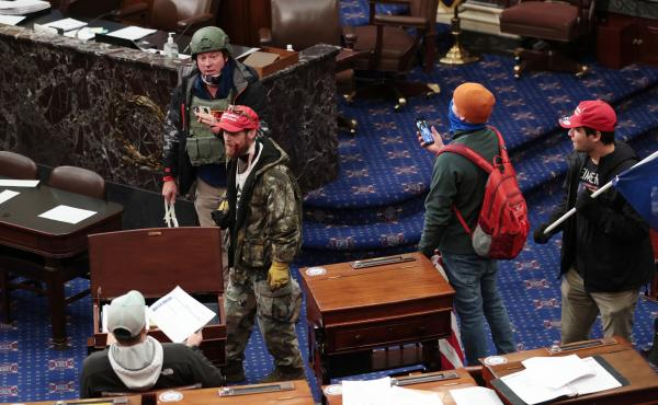 Larry Rendall Brock Jr., an Air Force veteran, is seen inside the Senate Chamber wearing a military-style helmet and tactical vest during the rioting at the U.S. Capitol. Federal prosecutors have alleged that before the attack, Brock posted on Facebook ab