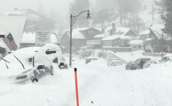 In this photo provided by Caltrans District 9, heavy snowfall blankets cars at June Lake, in Mono County, Calif., on Wednesday. The same storm that brought snow and heavy rain to the state is moving through the Midwest, with 5 to 9 inches of snowfall pred