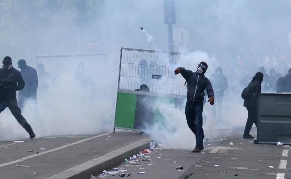 Masked protesters throw stones during clashes with French CRS riot forces at the May Day in Paris.