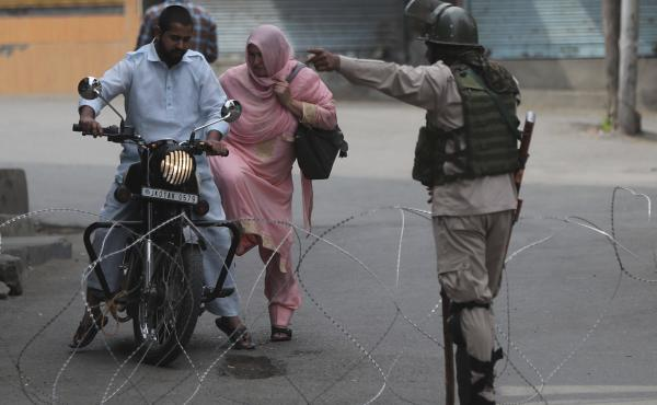 An Indian paramilitary soldier asks a Kashmiri couple on motorcycle to leave at a temporary checkpoint during restrictions in Srinagar, Indian-controlled Kashmir, on Friday.