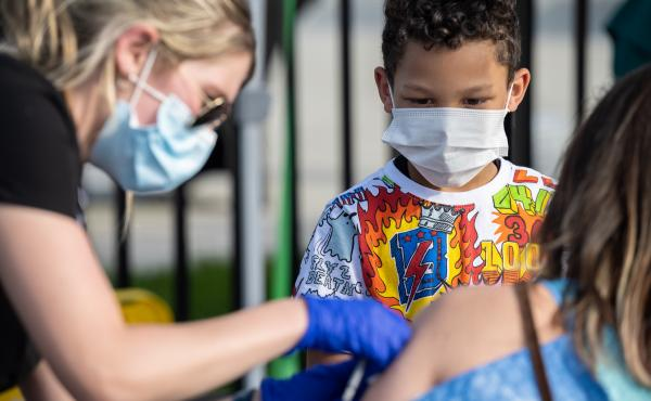 A child watches as a nurse administers a COVID-19 vaccine during a pop-up vaccination event in April at Lynn Family Stadium in Louisville, Ky.