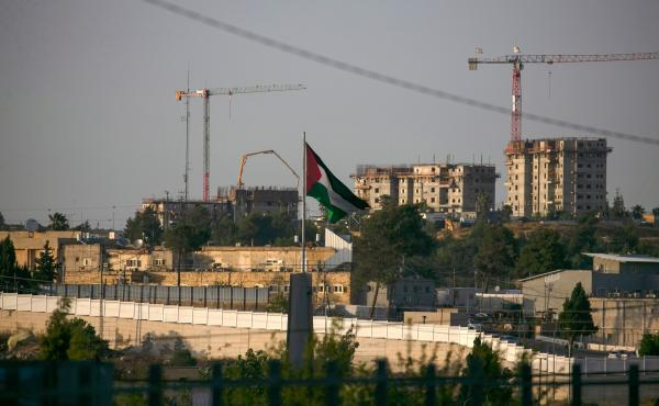 A Palestinian flag waves at the northern entrance to the city of Ramallah in the occupied West Bank as construction works take place in the Israeli settlement of Beit El in the background. Israel intends to annex West Bank settlements and the Jordan Valle
