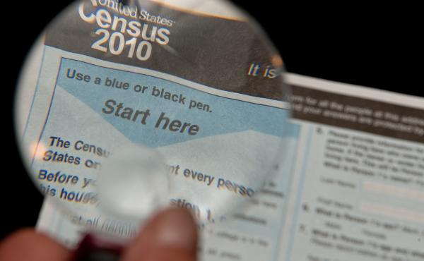A magnifying glass is placed over the 2010 Census questionnaire.