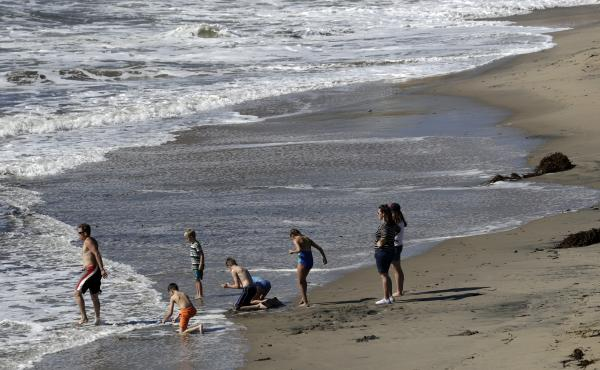 Beach goers wade in the surf at Natural Bridges State Beach in Santa Cruz , Calif. Public access to some beaches in California may be at risk with legal challenges to the California Coastal Act