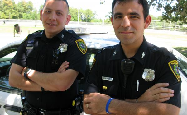 Officer Jesus Robles (at right) and Officer Jason Cisneroz, community service officers in the Houston Police Department, have noticed that fewer unauthorized Latinos step forward to report crimes out of fear of deportation.
