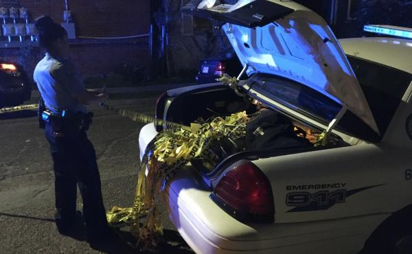 A New Orleans police officer strings up used crime scene tape at the scene of a drive-by shooting in the Central City neighborhood. One hundred people were shot in New Orleans by Feb. 10 — about a month sooner than recent years.