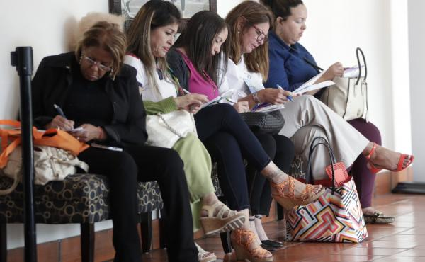 In this photo, women fill out job applications at a JobNewsUSA job fair in Miami Lakes, Fla.