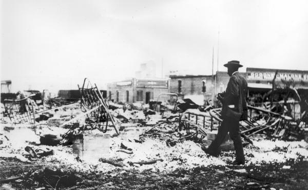 Photograph of an African-American man with a camera looking at the skeletons of iron beds which rise above the ashes of a burned-out block after the 1921 Tulsa Race Massacre, in Oklahoma.