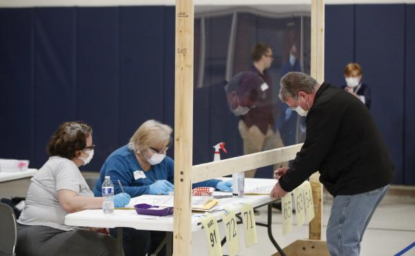 A man checks to cast his ballot in Kenosha, Wis., on April 7. A new study suggests that in-person voting in that Wisconsin primary did not produce a surge of new coronavirus cases.