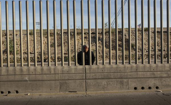 Issac Rodriguez, from Sinaloa, Mexico, peering through the fence that divides Mexico and the U.S. in Tijuana, Mexico.