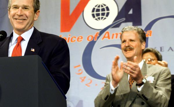 Robert R. Reilly led Voice of America briefly under President George W. Bush. Here they're shown at a VOA anniversary celebration in February 2002.