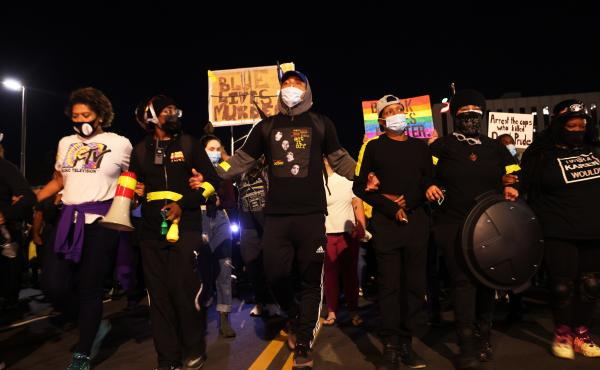 """Demonstrators lock arms as they march for Daniel Prude on Friday in Rochester, N.Y. Prude died after being arrested on March 23 by Rochester police officers, who had placed a """"spit hood"""" over his head and pinned him to the ground while restraining him."""