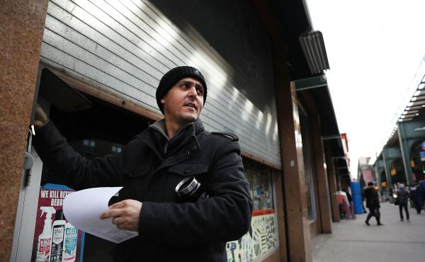 A Yemeni business owner closes the gate to his store Thursday in the Brooklyn borough of New York City. Across the city, Yemeni-owned bodega and grocery stores will shut down from noon to 8 p.m. to protest President Trump's executive order banning immigra