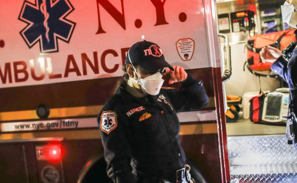 New York City Fire Department paramedic Elizabeth Bonilla (center) wears personal protective equipment after an emergency call in April in the Bronx borough of New York City. Bonilla is suing the city for allegedly retaliating against her and other EMS wo