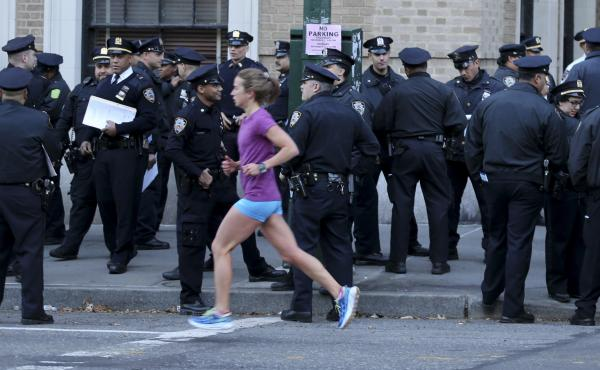 A runner moves past a group of police officers gathered near the finish line of the New York City Marathon on Nov. 6, 2016. Authorities are increasing the number of officers and other law enforcement personnel for this year's race, in the wake of an Tuesd