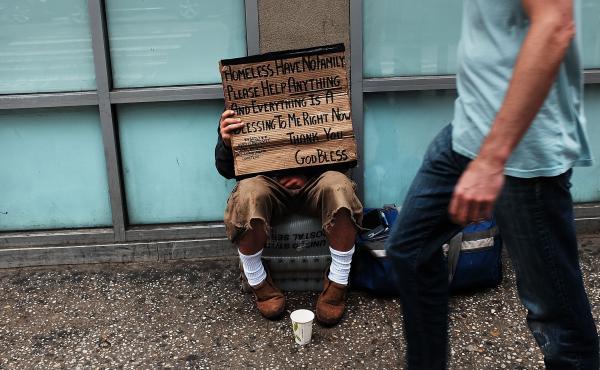 A homeless man panhandles along Manhattan's Eighth Avenue in New York City.