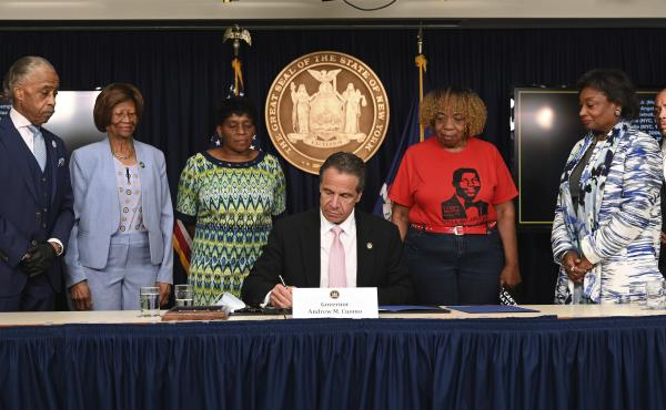 New York Gov. Andrew Cuomo, center, signs into law a sweeping package of police accountability measures on Friday that received new backing following protests of George Floyd's killing.