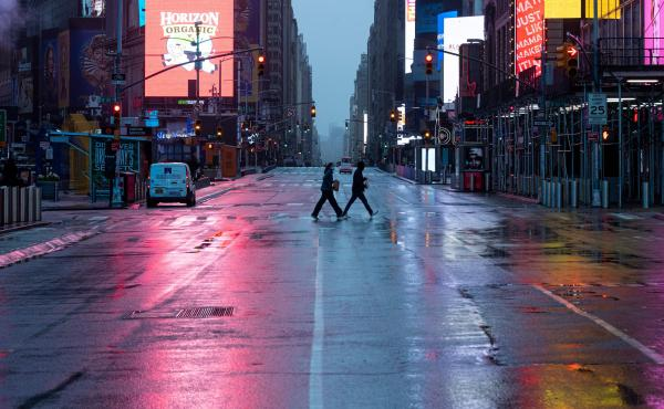 A couple wearing masks crosses the almost-deserted Times Square in New York City on Monday.