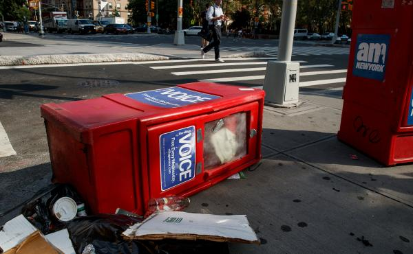 A Village Voice newspaper stand lays on the ground next to garbage in New York City's East Village on Tuesday. The Village Voice, one of the oldest and best-known alternative weeklies in the U.S., announced that it will no longer publish a print edition.