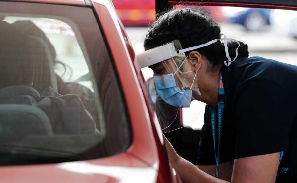 A Health worker administers vaccinations at a pop-up drive-in clinic Monday, Oct. 11, 2021, in Auckland, New Zealand. New Zealand's doctors and teachers are among those who must soon be fully vaccinated against the coronavirus to continue working in their