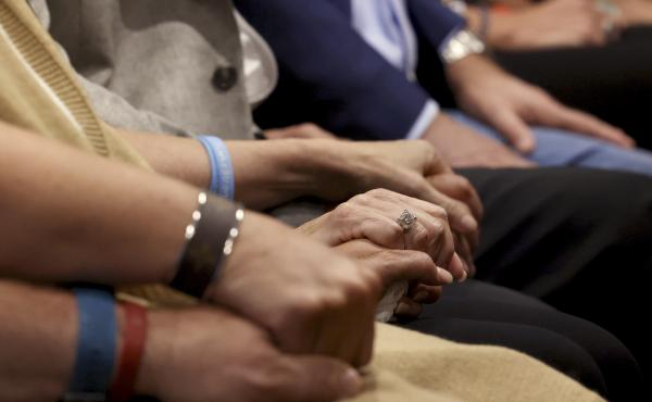 The Montalto and Hoyer families hold hands inside the Broward County Courthouse in Fort Lauderdale, Fla., on Wednesday, Oct. 20, 2021, during Marjory Stoneman Douglas High School shooter Nikolas Cruz's guilty plea in the 2018 shootings. The Montalto's dau