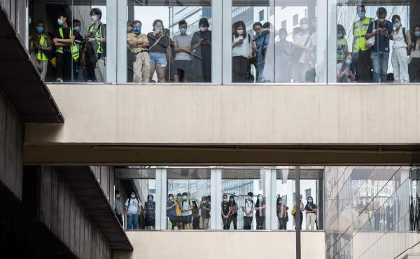Bystanders watch from footbridges Wednesday as riot police stand guard below outside a building in Hong Kong.