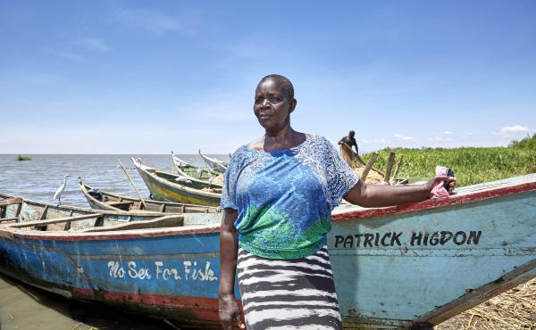 Justine Adhiambo Obura, chairwoman of the No Sex For Fish cooperative in Nduru Beach, Kenya, stands by her fishing boat. Patrick Higdon, whose name is on the boat, works for the charity World Connect, which gave the group a grant to provide boats for some
