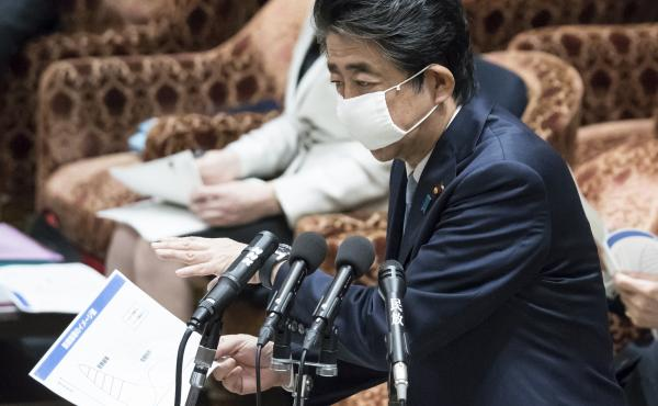 """Japan's Prime Minister Shinzo Abe, seen in parliament on Tuesday in Tokyo, said it would be """"impossible"""" to hold the already delayed Summer Olympics and Paralympics in 2021 if the disease is not brought under control."""