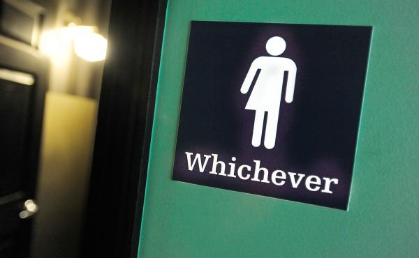 """A gender neutral sign is posted outside a bathrooms at Oval Park Grill in Durham, N.C. Many North Carolina businesses put gender neutral signs on toilets after the """"bathroom bill"""" was passed."""