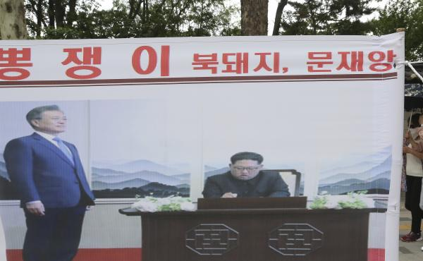 A banner showing a photo of North Korean leader Kim Jong Un and South Korean President Moon Jae-in, left, was displayed to denounce policies of Moon on North Korea in Seoul, South Korea.