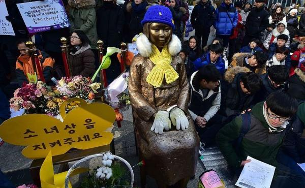 """During a weekly anti-Japanese demonstration, South Korean students sit near a statue of a teenage girl symbolizing former """"comfort women"""" who served as sex slaves for Japanese soldiers during World War II. The statue is seen in front of the Japanese Embas"""