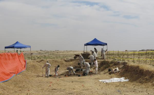 "Iraqi workers and international investigators excavate a mass grave known as ""the mother's grave"" in the Sinjar region of northern Iraq in October. The grave in the village of Solagh is believed to hold more than 80 bodies of women ISIS considered too old"